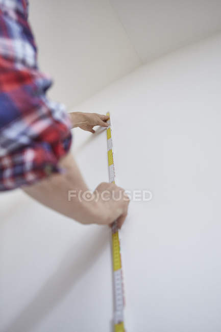 Cropped image of man measuring white wall — Stock Photo