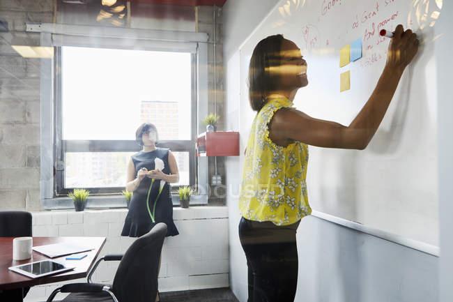 Deux femmes au bureau en utilisant le tableau blanc — Photo de stock