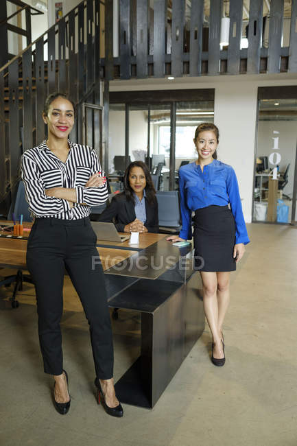 Portrait of three businesswomen in office smiling at camera — Stock Photo