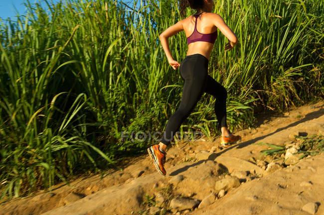 Female runner training on dirt track — Stock Photo