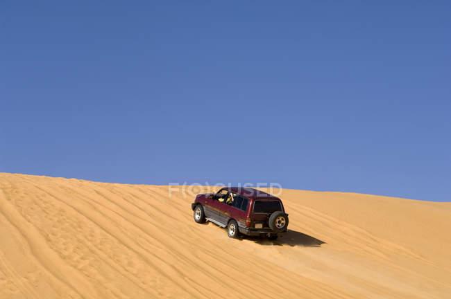 SUV on sand dunes, Erg Awbari, Sahara desert, Fezzan, Libya — Stock Photo