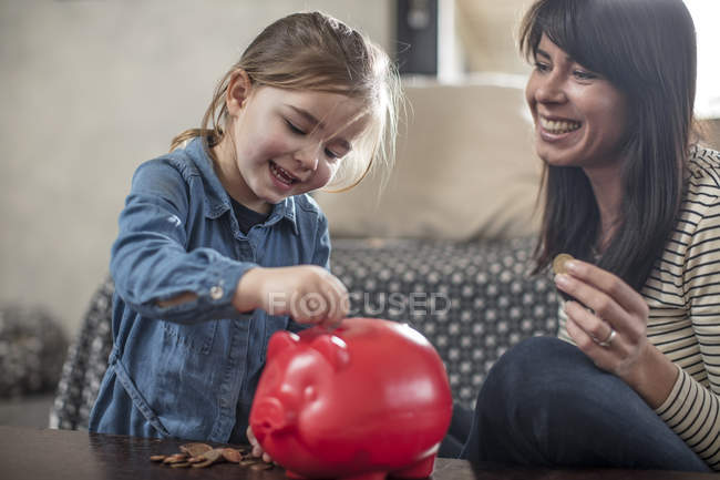 Mädchen einfügen Münzen im Sparschwein auf Couchtisch — Stockfoto