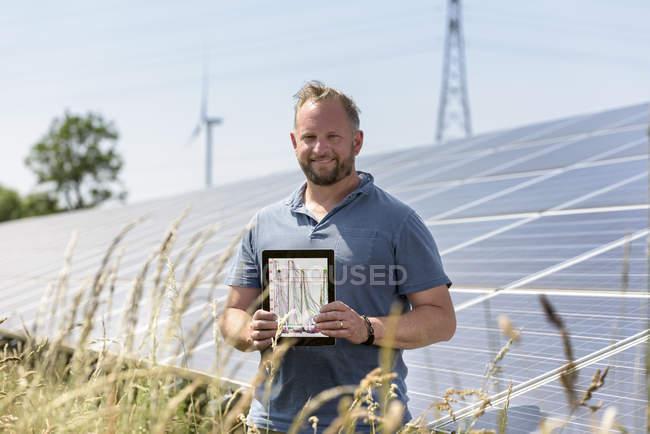 Community worker showing digital tablet app at solar farm — Stock Photo