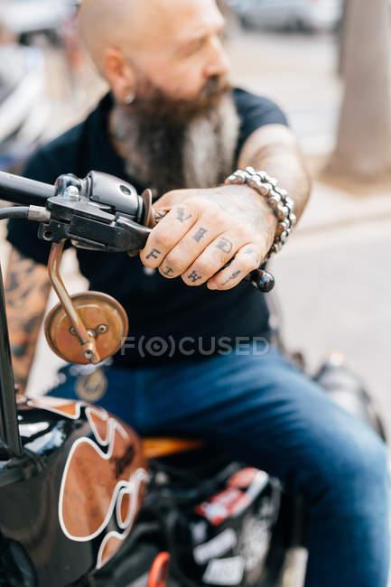 Maduro hombre hipster a caballo de la motocicleta, cerca de la mano tatuada - foto de stock