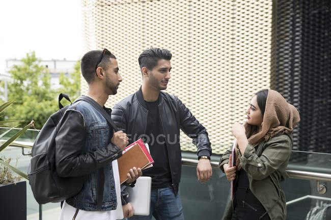 Three friends having conversation in street — Stock Photo