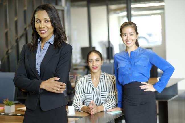Portrait of three businesswomen in open plan office — Stock Photo