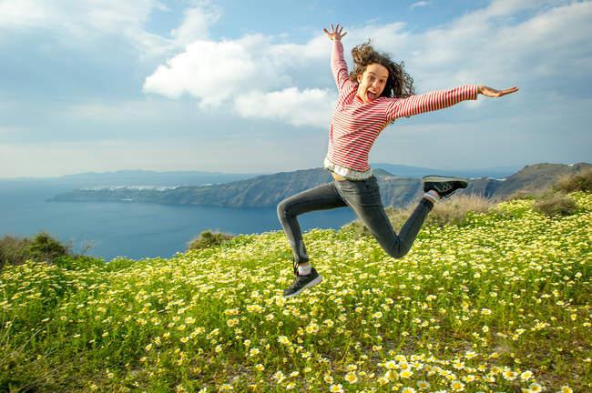 Девочка, прыгающая в воздухе над цветами, Санторини, Клайпеда, Греция — стоковое фото