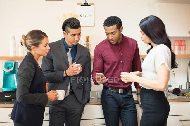 Jeunes collègues regardant smartphone dans la cuisine de bureau — Photo de stock