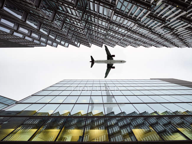 Low angle view of airplane flying  between modern buildings, London City Airport, London, UK — Stock Photo