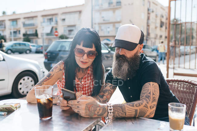 Mature hipster couple looking at smartphone at sidewalk cafe, Valencia, Spain — Stock Photo