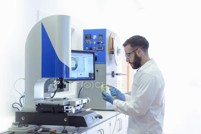 Вид збоку вченого, що працюють в лабораторії електромонтаж кабелю — стокове фото