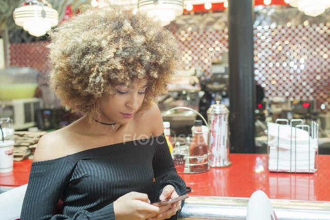 Jovem mulher sentada no restaurante e usando smartphone — Fotografia de Stock