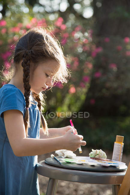 Side view of girl preparing paint palette in garden — Stock Photo
