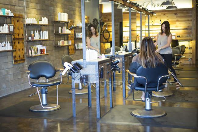 Cabeleireiro feminino trabalhando com cliente no salão — Fotografia de Stock