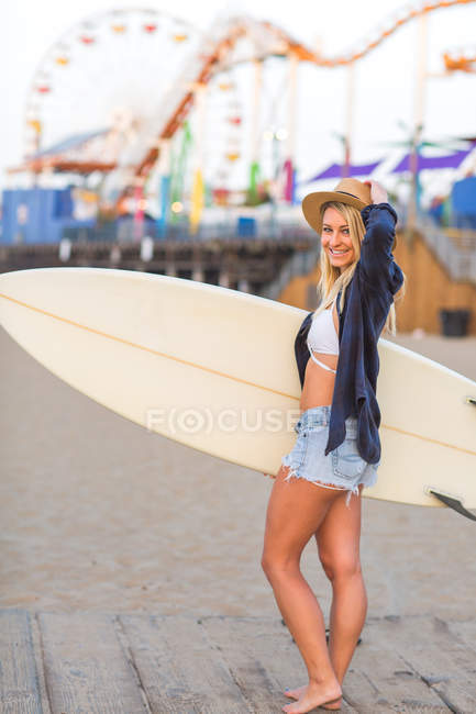 Portrait of young female surfer by amusement park on  beach, Santa Monica, California, USA — Stock Photo