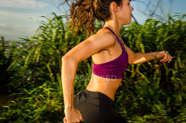 Side view of young female runner training outdoors — Stock Photo