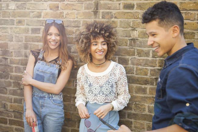 Drei lachende Freunde stehen zusammen in der Straße — Stockfoto