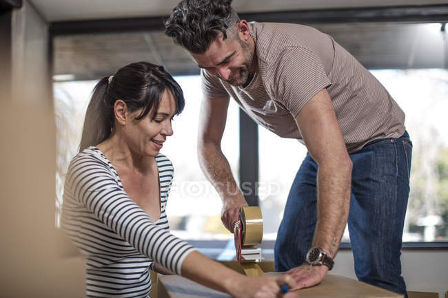 Couple packing belongings into cardboard box — Stock Photo