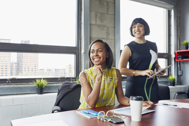 Two women in office looking away and smiling — Stock Photo