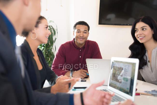 Jóvenes colegas trabajando juntos en la sala de reuniones - foto de stock