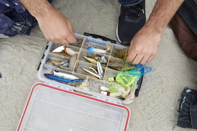 Manos de Fisher selección de gancho de pesca en la playa - foto de stock