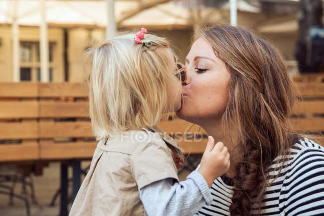 Мати дочка цілуватися малюк на лавки паркові — стокове фото