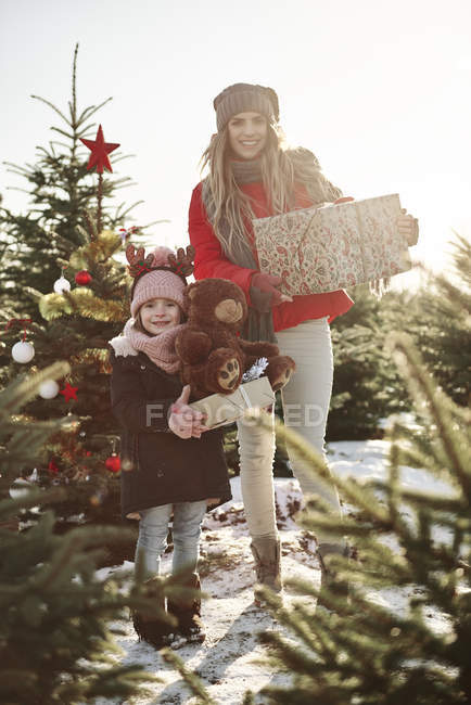 Girl and mother in christmas tree forest with christmas presents, portrait — Stock Photo
