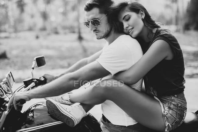 Молода жінка обійматися хлопець на мотоциклі — стокове фото