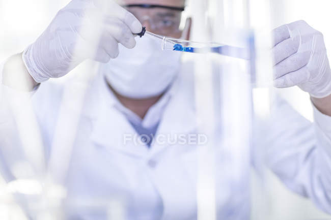 Laboratory worker using pipette to take liquid from test tube — Stock Photo