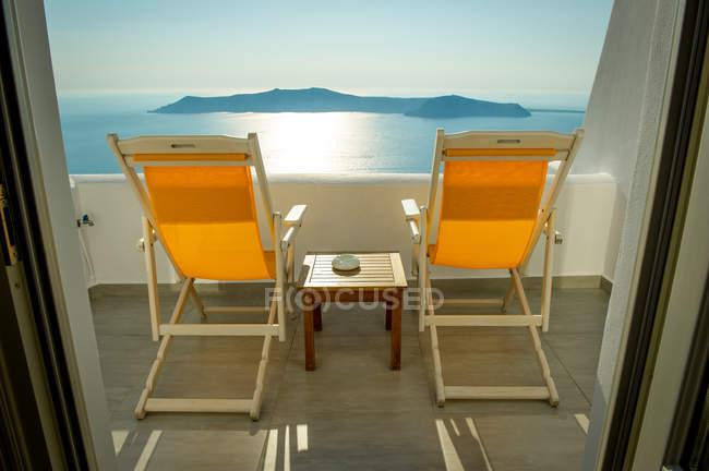 Sedie a sdraio sul balcone con vista mare, Oia, Santorini, Kikladhes, Grecia — Foto stock
