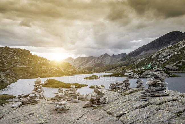 Stack di rocce in riva al lago al tramonto, San Bernardino, Ticino, Svizzera, Europa — Foto stock