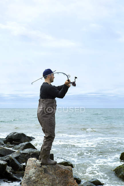 Young man on rock casting fishing rod to sea — Stock Photo