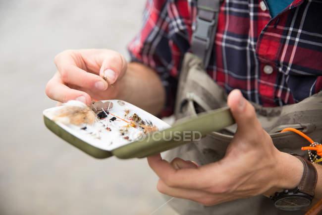 Uomo che prepara esca con pesca a Mosca sulle mani — Foto stock