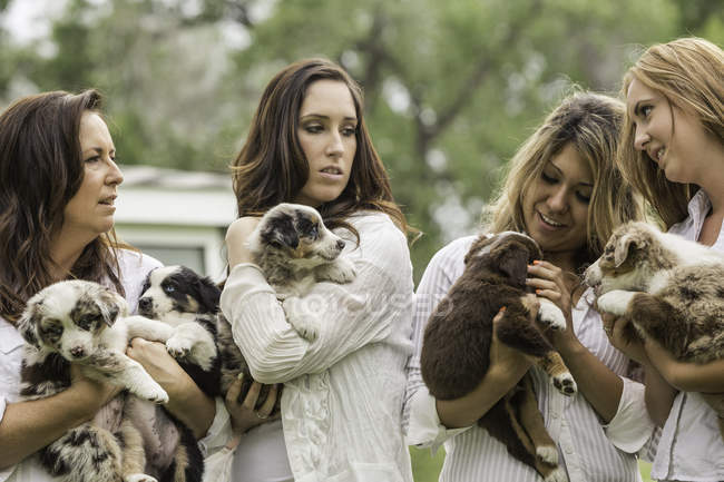 Young women and mature woman holding sheepdog puppies on ranch, Bridger, Montana, USA — Stock Photo