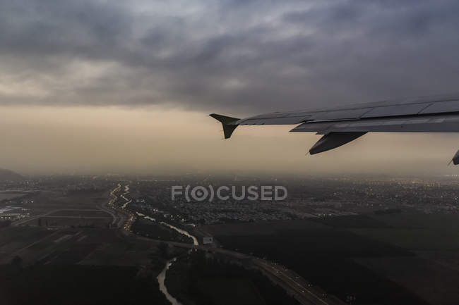 Airplane wing and aerial view of Punta Arenas city lights at dusk, Magallanes Region, Chile — Stock Photo