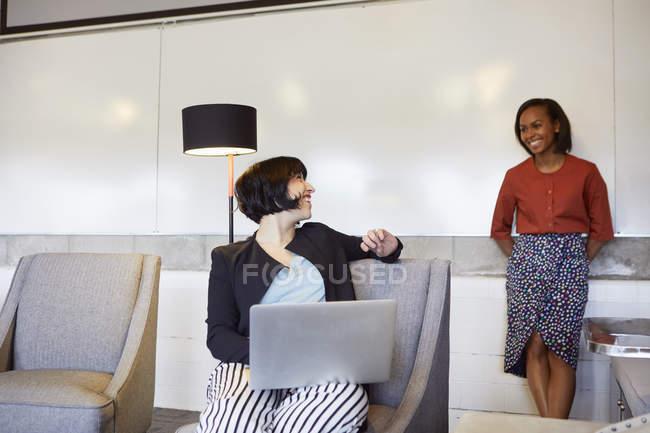 Femmes d'affaires travaillant avec ordinateur portable dans la salle de réunion — Photo de stock