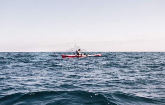 Молодой каякер смотрит на смартфон во время рыбалки, остров Санта-Крус, Калифорния, США — стоковое фото