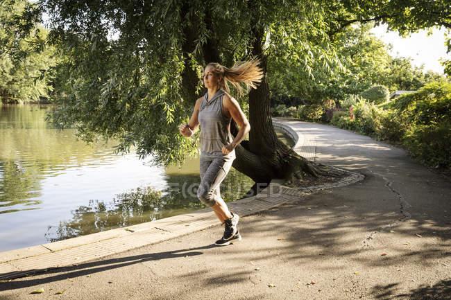Молодая женщина бежит по парковой дорожке — стоковое фото