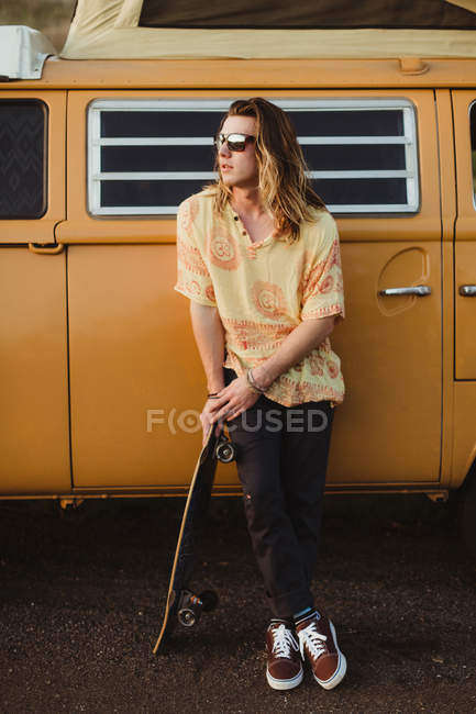 Young male skateboarder leaning against vintage recreational vehicle, Exeter, California, USA — Stock Photo