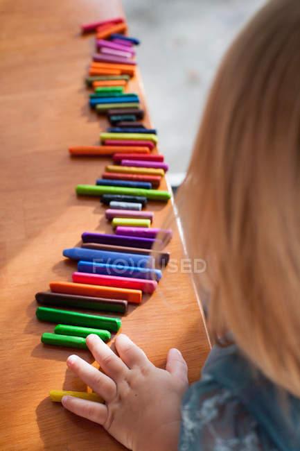 Fille aligner des crayons dans une rangée — Photo de stock