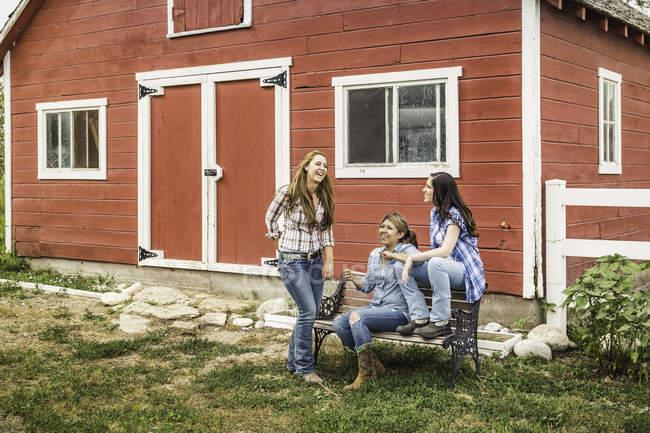 Três jovens mulheres rindo do lado de fora da fazenda, Bridger, Montana, EUA — Fotografia de Stock