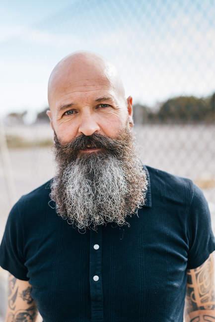 Portrait de mature hipster mâle avec une barbe grise devant la barrière métallique — Photo de stock