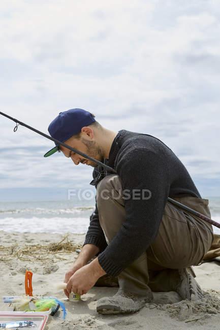 Hombre joven de cuclillas preparando anzuelo en playa - foto de stock
