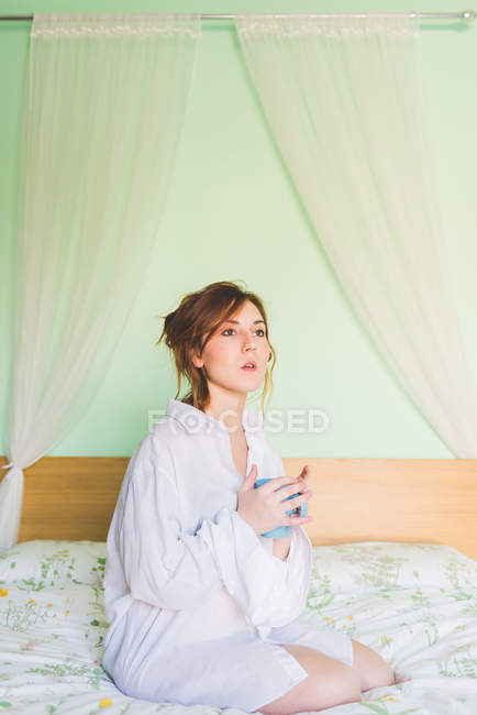 Junge Frau kniet auf dem Bett halten Kaffeetasse und starrte — Stockfoto
