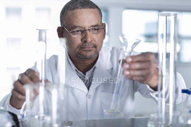Male Laboratory worker choosing measuring tube — Stock Photo