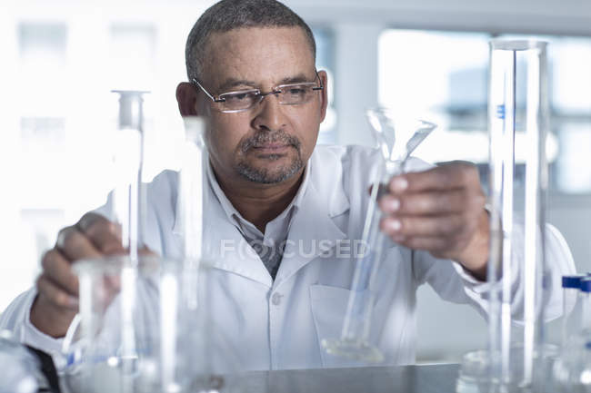 Male Laboratory worker choosing measuring tube — Stock Photo
