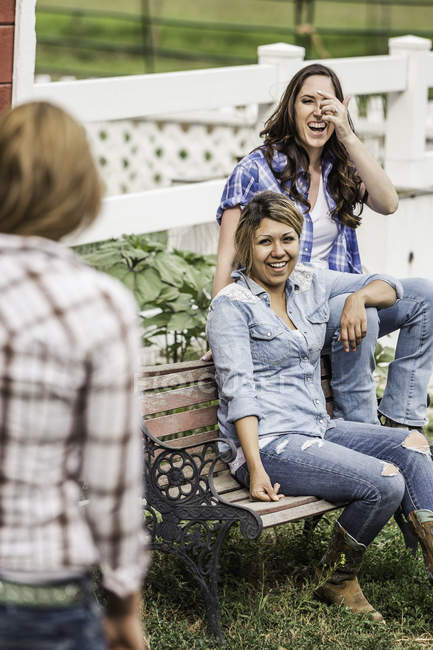 Three young women smiling in conversation outdoors — Stock Photo