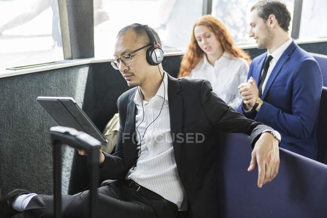 Businessman in headphones looking at digital tablet on passenger ferry — Stock Photo