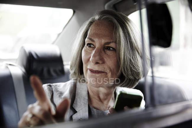 Старший предпринимательница сидит позади такси, держа смартфон, давая указания водителю — стоковое фото