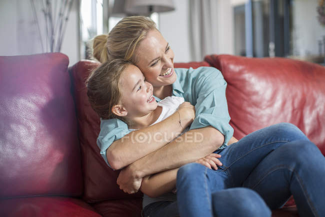 Мати і дочка на дивані обіймаються і посміхаються — стокове фото